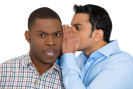 Closeup portrait of guy whispering into mans ear telling him something secret and disturbing. Shocked surprised disgusted annoyed mad response. Negative human emotions facial expression feelings photo
