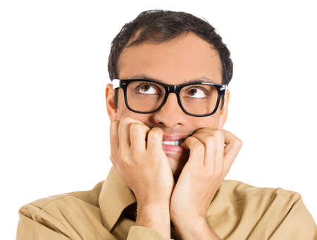 perfectionist: Closeup portrait of a nerdy guy, anxious man with big glasses, biting his finger nails craving something scared, looking up isolated on white background. Negative human emotions, facial expressions Stock Photo