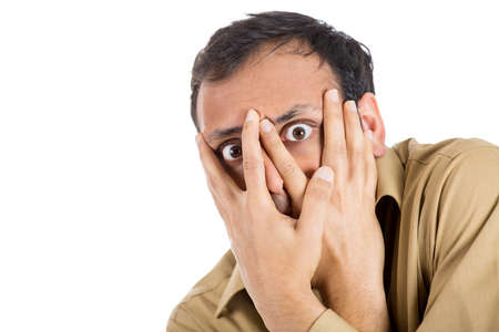 introvert: Closeup portrait of anxious guy, paranoid man covering his face with hands, looking through fingers, having panic attack, isolated on white background. Negative human emotions, expressions, attitude Stock Photo