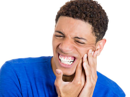 Closeup portrait of handsome young man, student, worker, teenager touching face having really bad pain, tooth ache, isolated on white background. Negative human emotions, facial expressions, feelings. photo