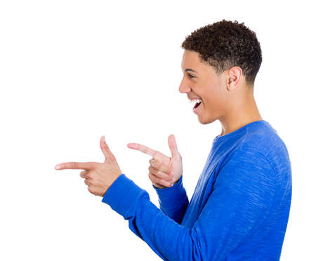 hilarity: Closeup side view profile portrait of young man, laughing, pointing with finger at someone or something, isolated on white background. Positive face expressions, emotions, feelings, attitude, approach