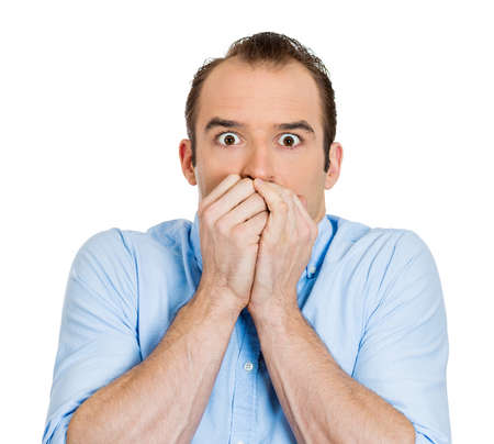 perfectionist: Closeup portrait of scared anxious, funny looking young guy, terrified business man covering mouth with hands, wide opened eyes looking at you camera, isolated on white background. Facial expressions. Stock Photo