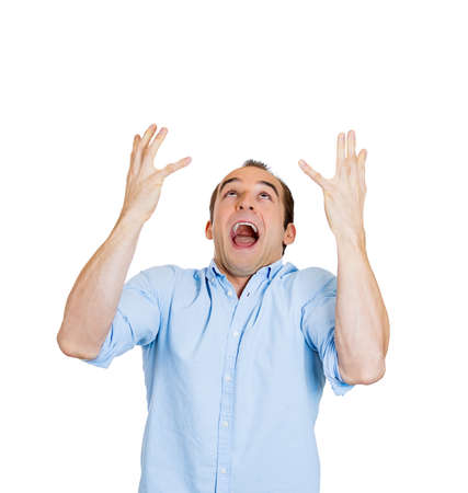 Closeup portrait of frustrated young man fed up with the world, hands in air looking up screaming, isolated on white background. Negative emotion facial expression feelings, reaction, perception photo
