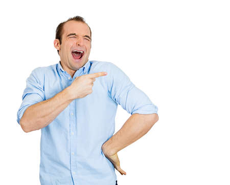 hilarity: Closeup portrait of young man, laughing, pointing with finger, arms at someone, something, isolated on white background. Positive human face expression, emotion, feelings, attitude, approach, reaction