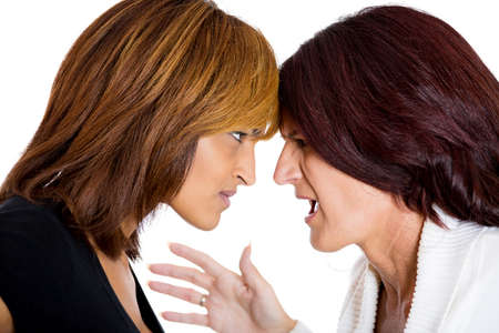 resentment: Closeup portrait of two mad angry women with bad attitudes getting into an argument about to fight, isolated on white background. Interpersonal conflict. Negative emotions facial expression feeling