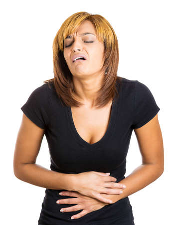 doubled: Closeup portrait of a young stressed woman placing hands on stomach having bad aches and pains, isolated on a white background. Food poisoning, influenza, cramps. Negative emotion facial expressions