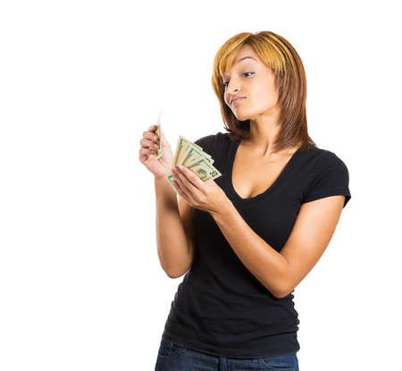 possessive: Closeup portrait of greedy possessive young woman counting money dollar bills in hand, isolated on white background. negative emotion facial expression feeling. Financial reward savings Stock Photo