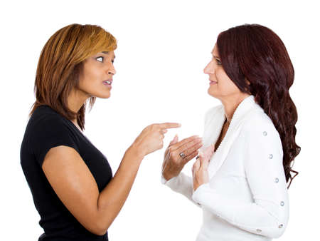 slander: Closeup portrait of two angry upset women, one blames the other for something wrong who is surprised offended, isolated on white background. Negative emotion facial expression. Interpersonal conflict Stock Photo