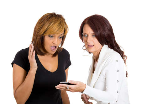 bummed: Closeup portrait of two women looking shocked upset while watching something on their cell phone, a text message, sms or email, isolated on white background. Negative emotion facial expression feeling Stock Photo