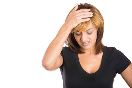 premenstrual: Closeup portrait of young woman having really bad headache pain placing hand on head and hair looking down, isolated on white background copy space to left. Negative human emotion facial expressions