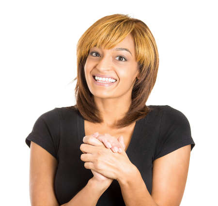 gratified: Closeup portrait of grateful happy young woman smiling with hands clasped close to chest, isolated on white background with copy space to left. Positive human emotion facial expressions Stock Photo