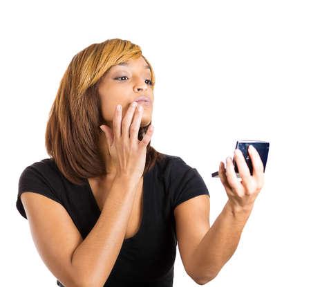 snobby: Closeup ritratto di giovane arrogante bella donna in cerca ammirando il suo viso ei capelli davanti allo specchio della tasca, isolato su sfondo bianco. Emozione negativa sentimento espressione del viso