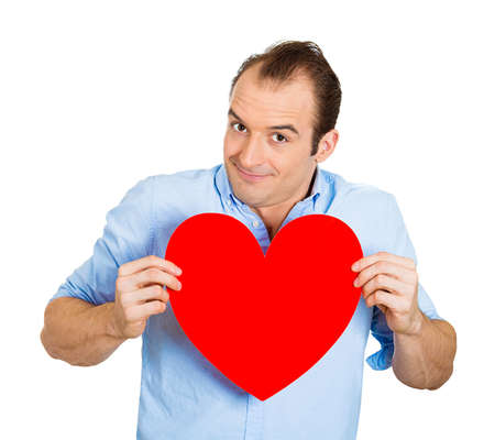 adoring: Closeup portrait of happy smiling handsome funny looking man, holding large red heart to chest daydreaming of women in love, isolated on white background. Positive emotions, facial expression feelings
