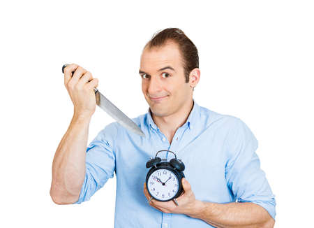 postpone: Closeup portrait of young funny looking guy, sarcastic arrogant happy business man holding knife, alarm clock, mercilessly killing time, isolated on white background. Human face expressions, emotions