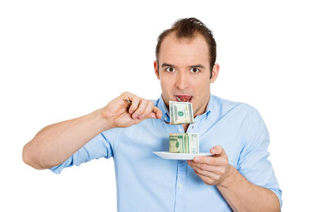 pennypinching: Closeup portrait of greedy, evil young ceo man in blue shirt eating green cash dollars from plate, isolated on white background. Negative emotion, facial expression feelings. Financial avarice concept