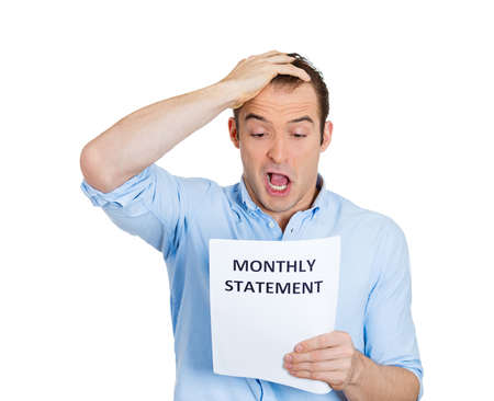 Closeup portrait of sad, shocked funny looking young man disgusted at his monthly statement, isolated on white background. Negative human emotion facial expression feelings. Financial crisis, bad news Stock Photo