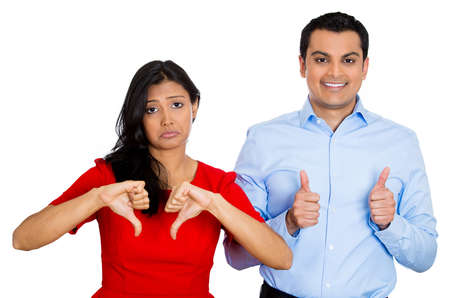 Closeup portrait of conflict couple, man woman. One excited happy smiling optimistic, showing thumbs up, other serious concerned unhappy thumbs down, isolated on white background. Emotion contrasts Stock Photo