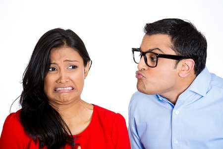 snobby: Closeup portrait of nerdy young man with big black glasses trying to kiss snobby woman who is grossed out, disgusted funny smirk on face, isolated white background. Negative emotion facial expression