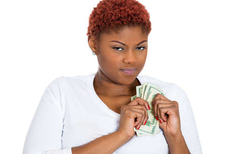 miserly: Closeup portrait of grumpy greedy miserly young woman, protecting money, holding dollar bills in hands, looking anxiously with suspicion, isolated white background. Negative human emotions expressions