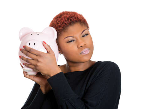 bad economy: Closeup portrait of poor stressed, upset, sad, unhappy young woman listening to empty piggy bank, isolated on white background. Financial difficulties, bad economy debt concept. Negative emotion