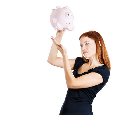 Closeup portrait of young pretty woman holding piggy bank upside down searching for money, completely broke, isolated on white background. Negative emotion facial expression feelings. Bad finances photo