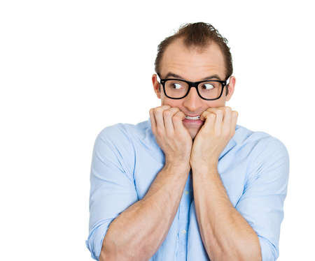 Closeup portrait of nervous stressed young nerdy guy, funny man with eyeglasses biting fingernails looking anxiously craving something isolated on white background. Negative emotion expression feeling photo