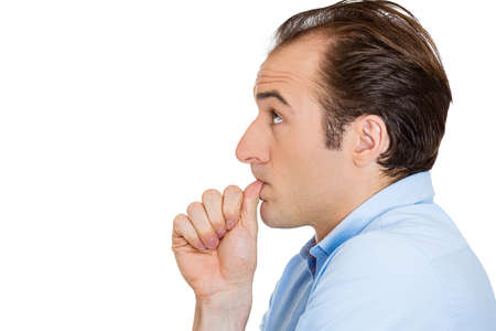 Closeup side view profile portrait of man with finger in mouth, sucking thumb, biting fingernail in stress, deep thought, isolated on white background. Negative emotion, facial expression, feelings Stock Photo - 26104895