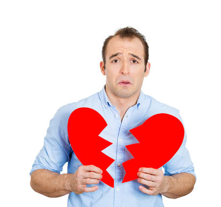 bereavement: Closeup portrait of young, troubled, sad, confused man, holding broken heart in his hands, about to cry, isolated on white background. Negative human emotions, facial expressions, feelings, attitude