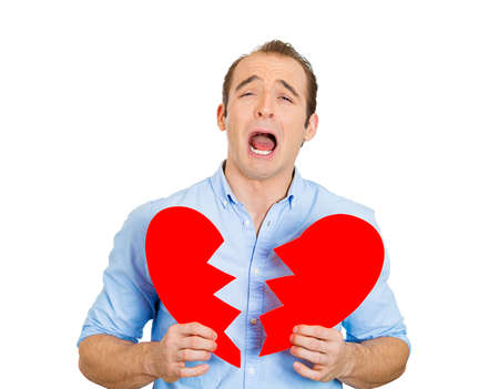 betrayal: Closeup portrait of young troubled sad crying, funny looking man, guy holding broken heart in hands isolated on white background. Negative human emotion, facial expression, feelings, attitude reaction Stock Photo
