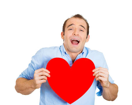 vulnerable: Closeup portrait of happy smiling handsome funny looking man, holding large red heart to chest daydreaming of women in love, isolated on white background. Positive emotions, facial expression feelings