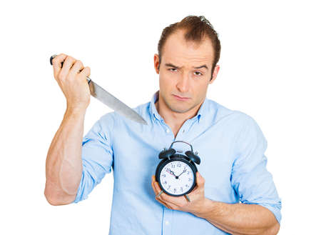 postpone: Closeup portrait of young funny looking guy, sarcastic arrogant business man holding knife and alarm clock, mercilessly killing time, isolated on white background. Human face expressions, emotions