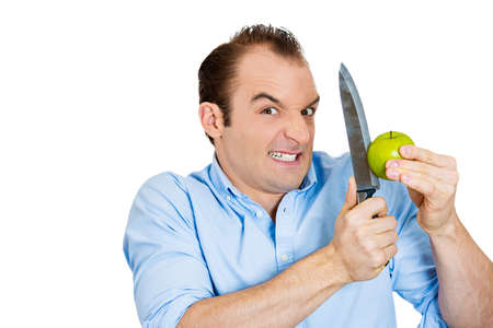 genetically engineered: Closeup portrait of crazy, funny looking business man, executive, manufacture CEO, politician, madly cutting green organic apple with knife isolated on white background. Human face expression, emotion