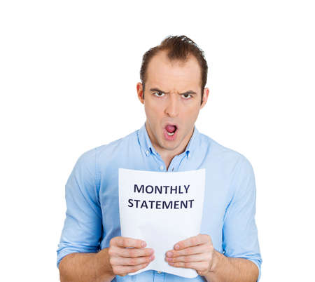 bank records: Closeup portrait of sad, shocked funny looking young man disgusted at his monthly statement, isolated on white background. Negative human emotion facial expression feelings. Financial crisis, bad news Stock Photo