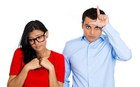 submissive: Closeup portrait of couple. Bully husband, man standing  upfront angry, loser sign on head, shy wife, nerdy woman wearing glasses looking downwards, isolated on white background. Human emotion culture