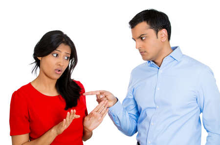 domestic: Closeup portrait of stressed, arguing young couple having serious problems fighting, isolated white background. Woman victim of domestic violence and abuse. Husband placing blame and pointing fingers Stock Photo