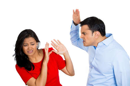 Closeup portrait of stressed, arguing young couple having serious problems fighting, isolated on white background .Woman victim of domestic violence and abuse. Husband man about to beat his wife