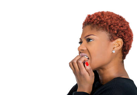 Closeup side view portrait of young unhappy, scared woman anxious female biting nails looking with craving, envy for something, worried, isolated on white background. Human face expressions, emotions