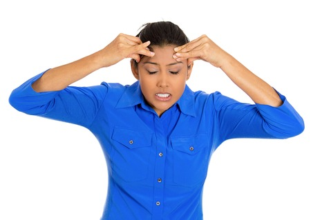 Closeup portrait of worried young woman having really bad headache hurt pain placing both hands on temples, isolated on white background. Negative emotion facial expressions feelings, body language Stock Photo