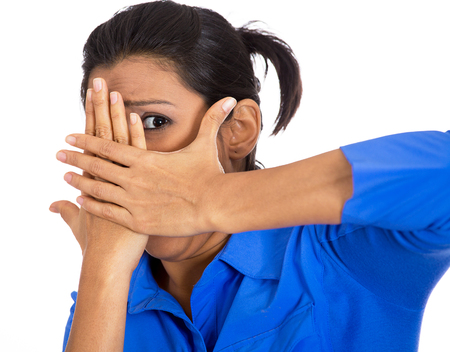 avoid: Closeup portrait of young scared terrified horrified shocked woman peeking through covered hand, cant believe what she sees, isolated on white background. Negative emotion facial expression feelings.