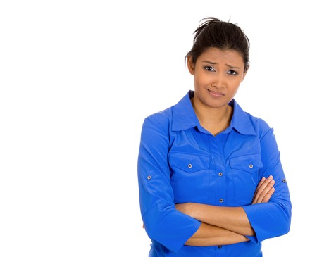 Closeup portrait of skeptical young woman with arms crossed looking suspicious disgusted on face, mixed with disapproval, isolated white background. Negative human emotion, facial expression, feelings