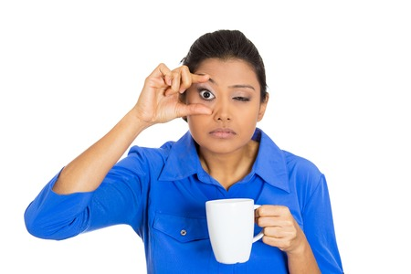 Closeup portrait of very tired falling asleep young woman, student holding cup of coffee struggling not to crash stay awake, keeping eyes opened, isolated on white background. Human face expression