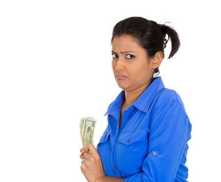 tightly: Closeup portrait of greedy young woman corporate business employee, worker, student holding dollar banknotes tightly, isolated on white background. Negative human emotion facial expression feeling