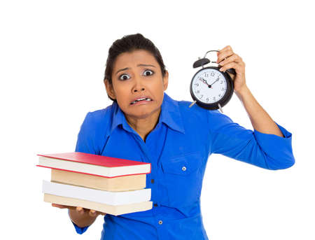 Closeup portrait of busy nervous young woman carrying tons of books and clock, stressed from project deadline, isolated on white background. Negative emotion facial expression feelings, body language photo