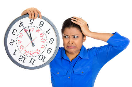 test deadline: Closeup portrait of a business woman, student, leader holding a clock very stressed, pressured by lack of and running out of time late for a meeting, isolated on a white background. Negative emotions