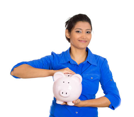 Closeup portrait of young smiling school student, worker woman holding piggy bank, isolated on white background. Smart currency financial investment wealth decisions. Budget management and savings photo
