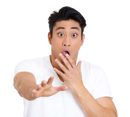 blown away: Closeup portrait of young man, looking shocked, surprised in disbelief, covering his mouth and hand outward at someone, isolated on white background. Negative human emotions, facial expressions