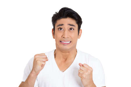 fidgety: Closeup portrait of tensed young man, fists in air, anxiously anticipating awaiting something bad will happen in future, isolated on white background. Negative emotion facial expression feelings.