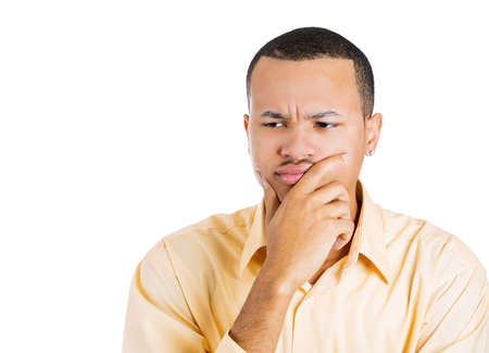 reconsider: Closeup portrait of unhappy young man thinking daydreaming deeply bothered by something hand on face looking downwards, isolated on white background. Negative emotion facial expression feeling Stock Photo