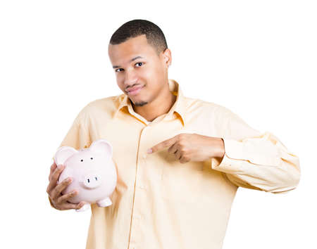Closeup portrait of young smiling school student, worker man holding pointing to piggy bank, isolated white background. Smart currency financial investment wealth decisions. Budget management, savings photo