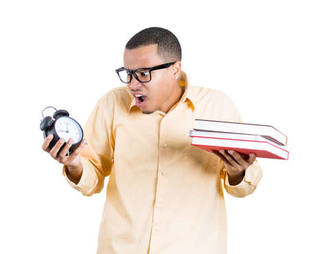out time: Closeup portrait of a nerdy business man, student, holding a clock and books stressed, pressured by lack of and running out of time late for a meeting, isolated  white background. Negative emotions